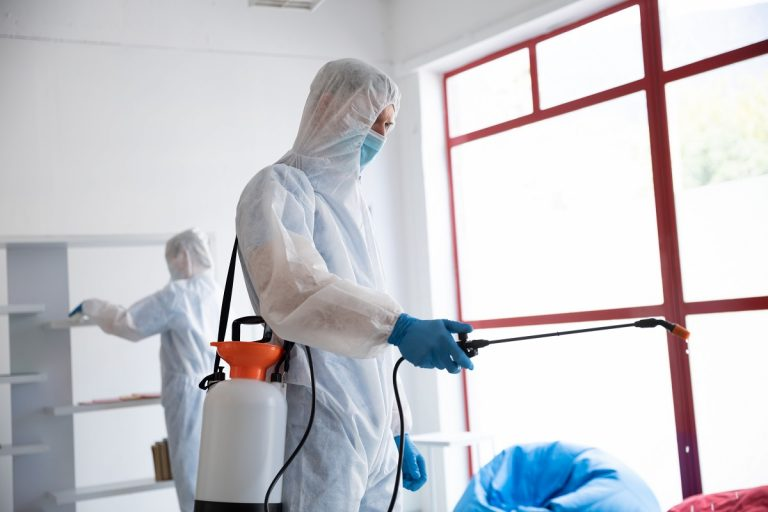 Caucasian male doctor scientist wearing protective clothing and face mask, cleaning, spraying disinfectant all over the place. Coronavirus covid 19 pandemic biohazard.